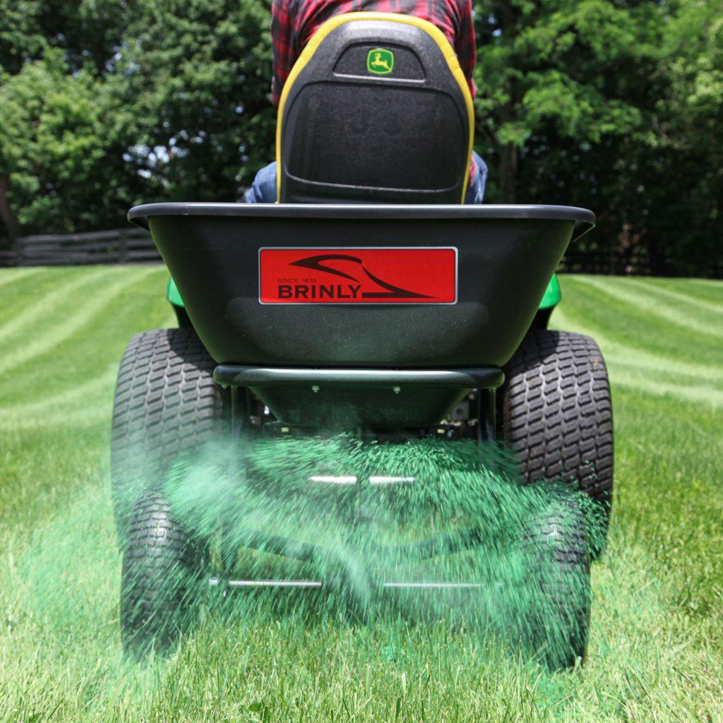brinlg garden spreader spraying green seed