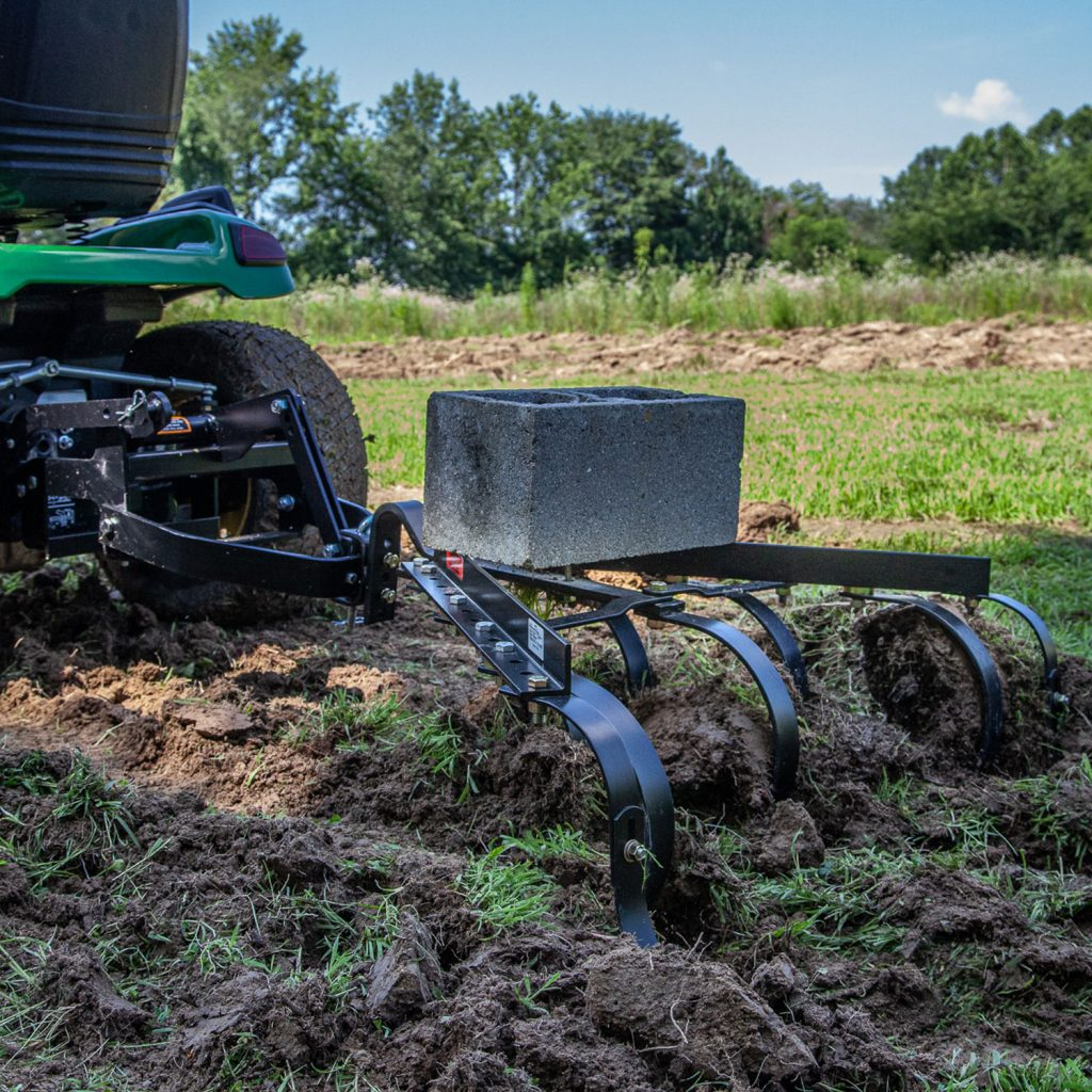 tow cultivator breaking up farm plot with cement weight