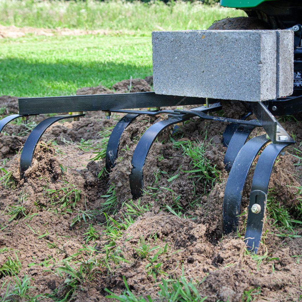 brinly cultivator breaking garden ground with cement weight