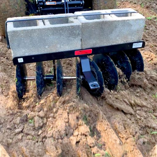 brinly disc harrow discing ground with cement weights